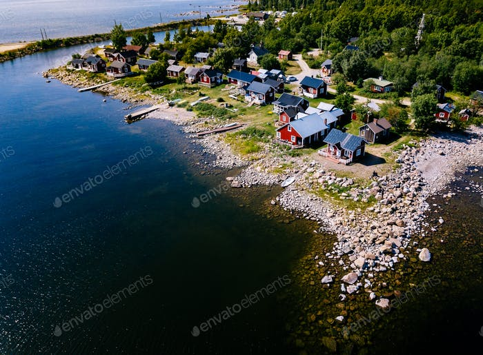 Red wooden houses on the lake or sea coast. Fishing village in Finland