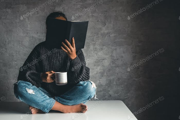 Girl in jeans with a cup of coffee on the table reads books. Education, Development