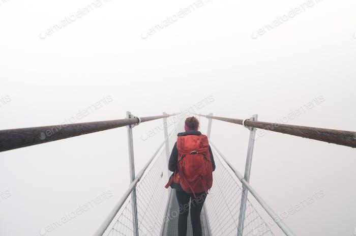 Female tourist walking across a suspension bridge in heavy fog
