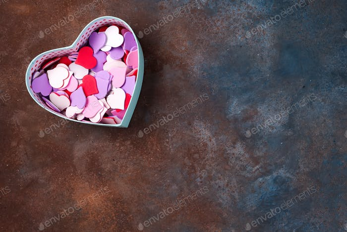 Open empty gift box with a hearts shape on stone background, flat lay