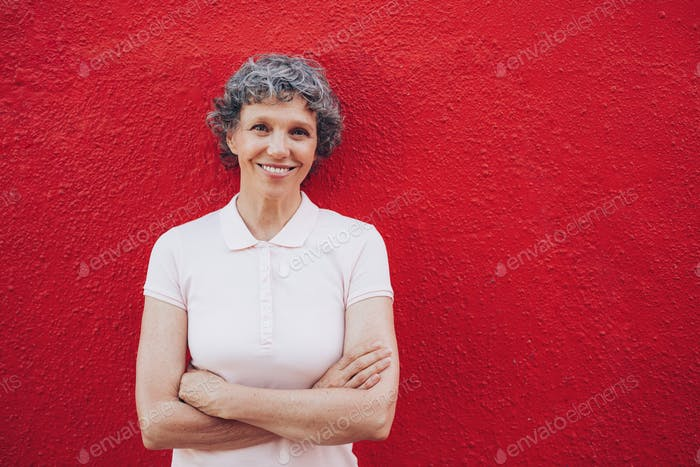 Portrait of happy mature woman against red wall