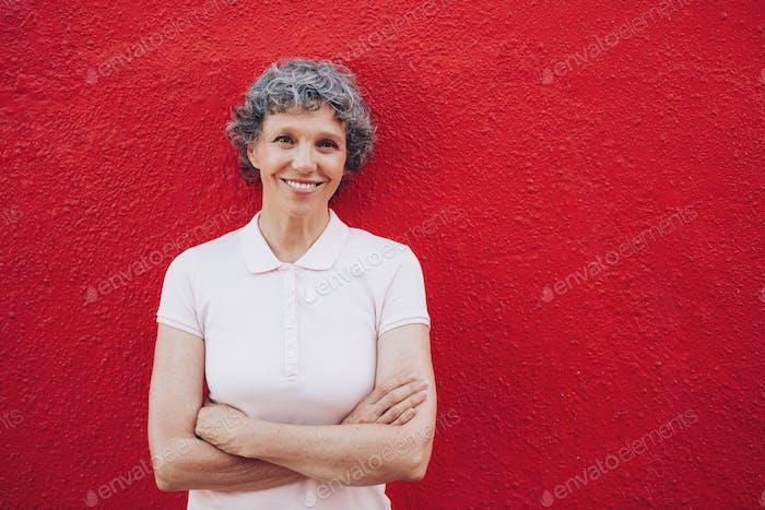 Porträt von glücklich reife Frau gegen rote Wand