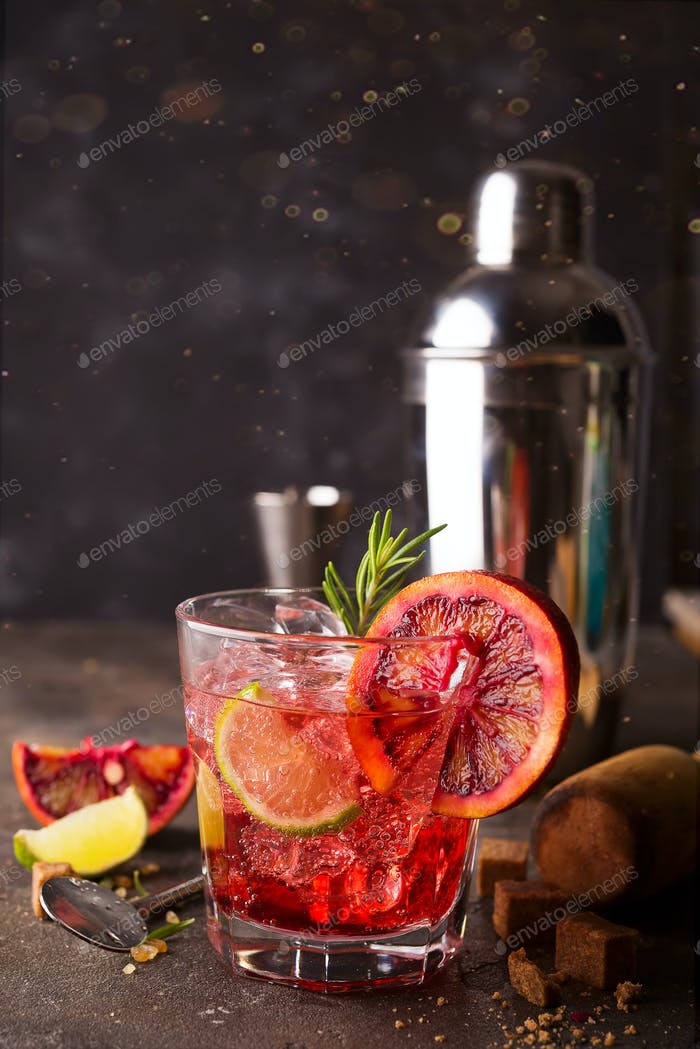 Negroni cocktail standing on the stone background and served with cubes of brown sugar