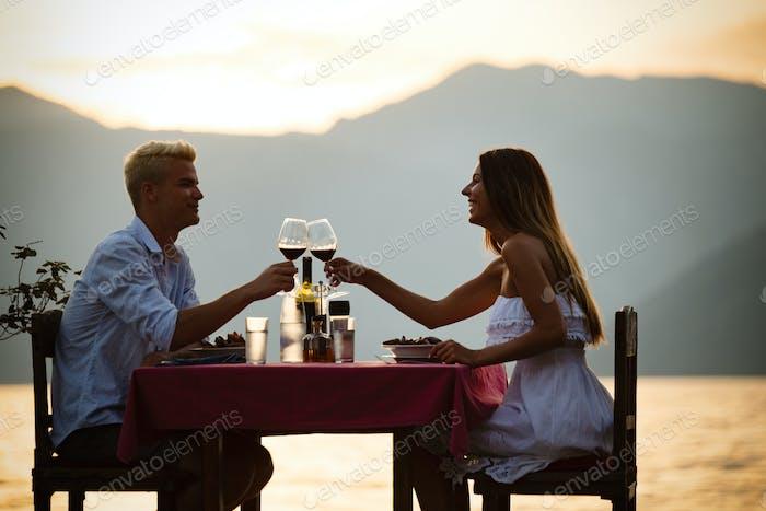 Happy couple on summer evening having romantic dinner outdoor