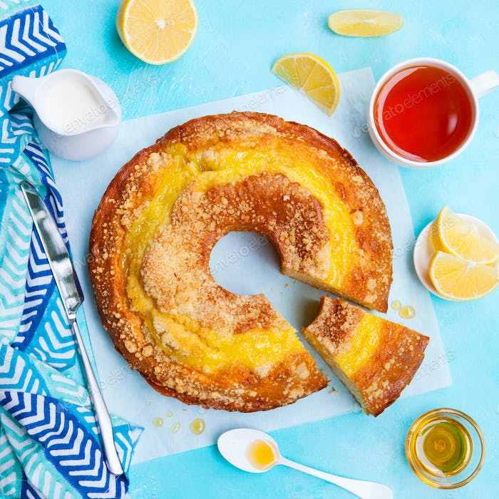 Lemon Bundt Cake with Cup of Tea. Blue Background. Top View.