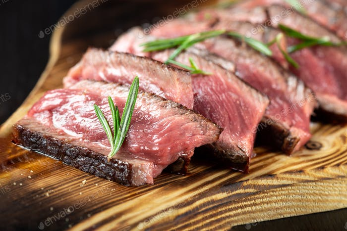 Juicy Beef Rib Eye Steak slices slightly salted, with herbs and spices on wooden board