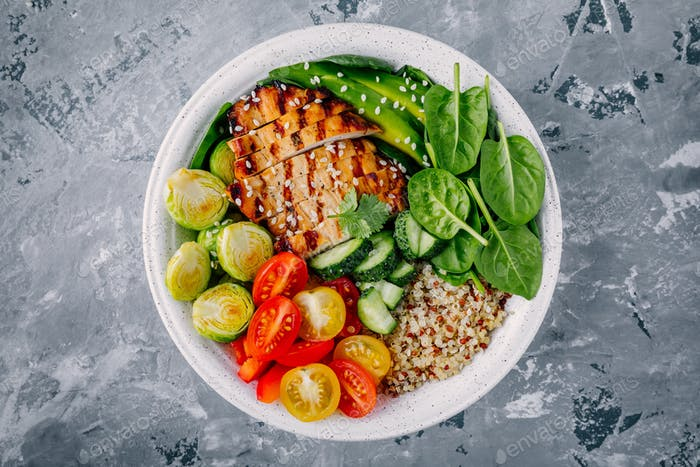 Healthy bowl with grilled chicken, quinoa, spinach, avocado, brussels sprouts, tomatoes, cucumbers
