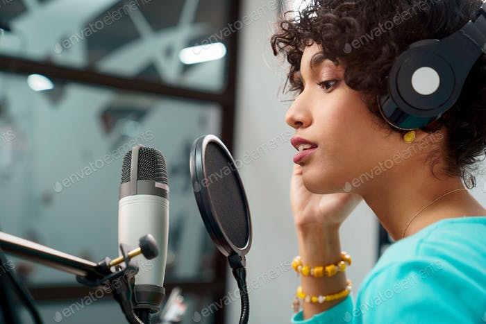 Attractive African American Young Woman Singing Into Microphone in Studio