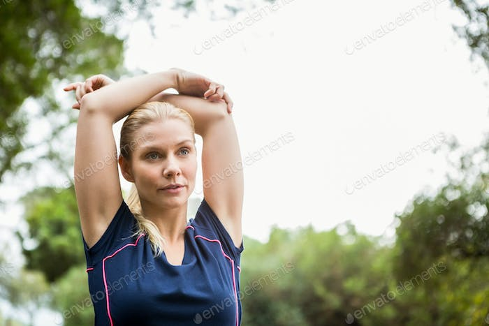 Serious athletic woman doing arms stretching