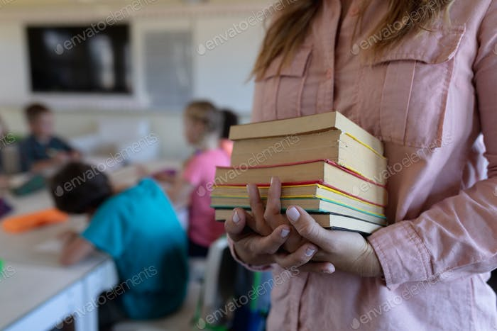 Female teacher standing in a classroom  holding a pile of books