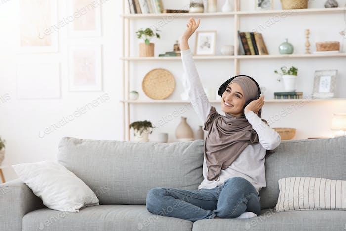 Fröhlicher Tag. Positive arabische Mädchen In Hijab Musik hören In drahtlosen Kopfhörern