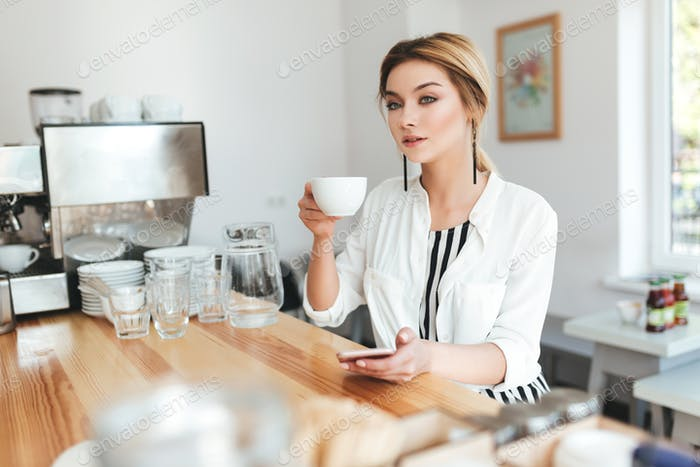 Beautiful lady with blond hair sitting at the counter and drinking coffee in coffee shop