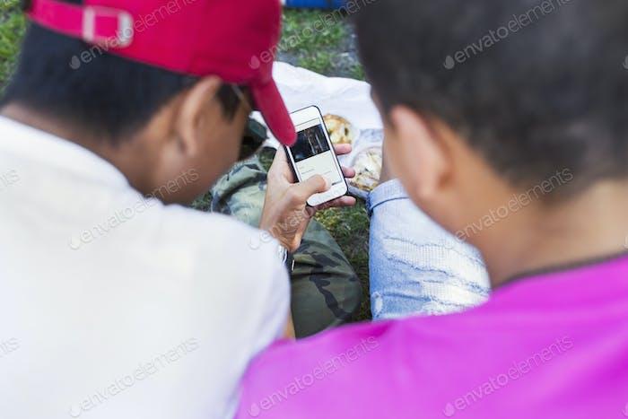 Rückansicht von Teenager-Jungen (14-15) mit Blick auf Smartphone