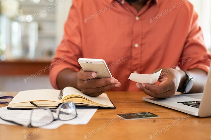 Man hands using smartphone and holding receipt