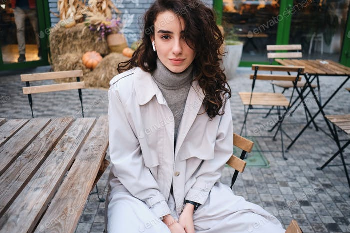 Attractive stylish brunette girl in trench coat dreamily looking in camera in cafe on city street