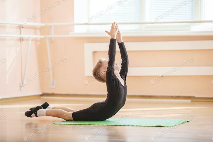 Boy dancer doing exercise at ballet dance class