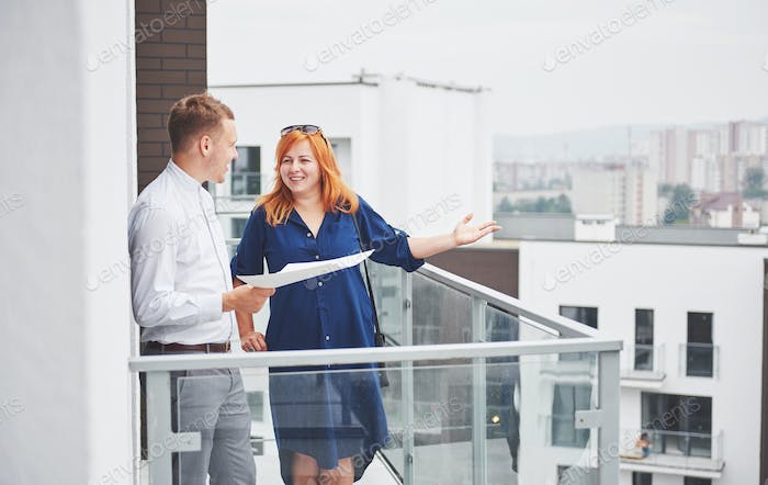 An engineer showing blueprint to her client