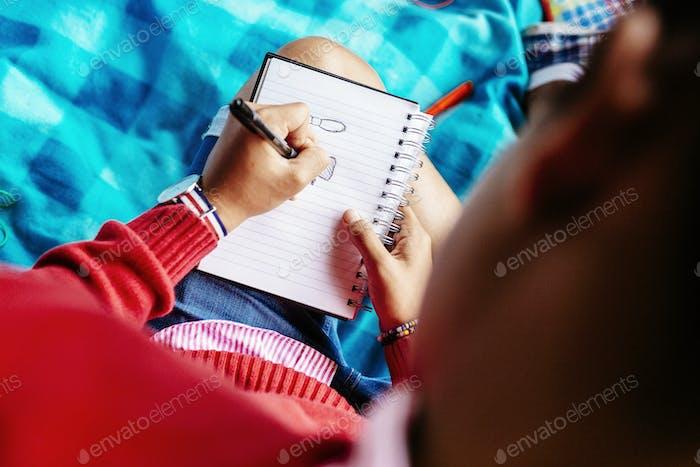 Hochwinkelansicht von Studenten, die im Tagebuch im Park schreiben