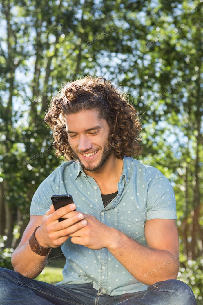 Young man using smartphone in the park on a summers day