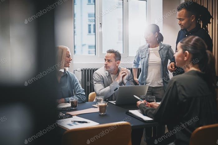 Businesspeople going over work together during an office meeting
