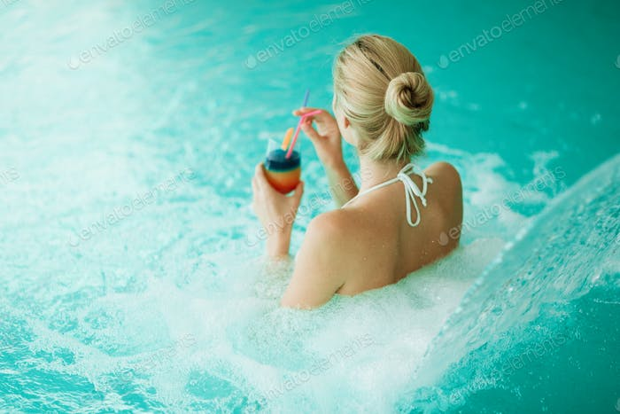 Woman enjoying hydrotherapy and cocktail