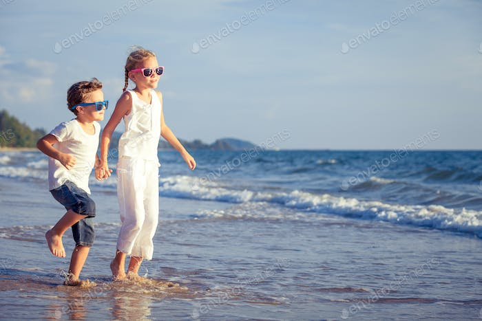 Happy children playing on the beach at the day time.