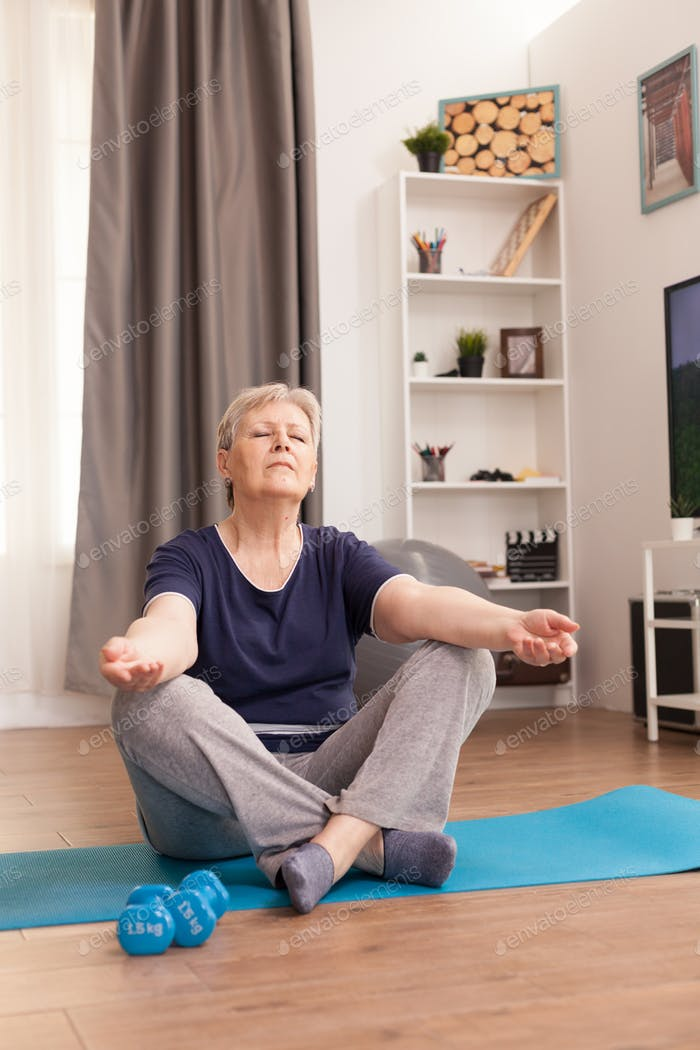 Aged woman practicing yoga at home