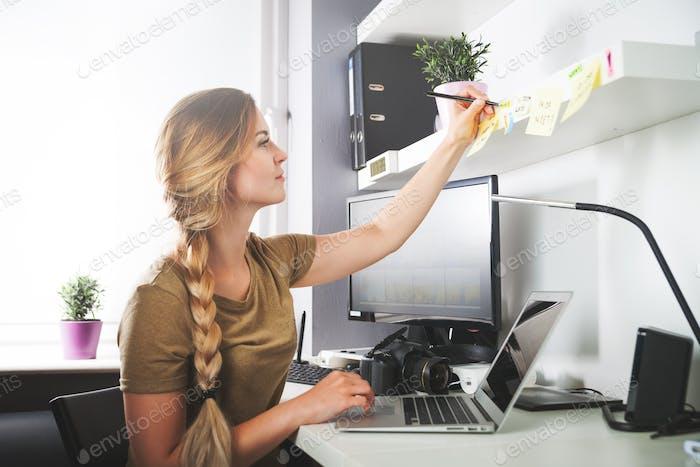 Frau arbeitet im Heimbüro am Computer und macht sich Notizen