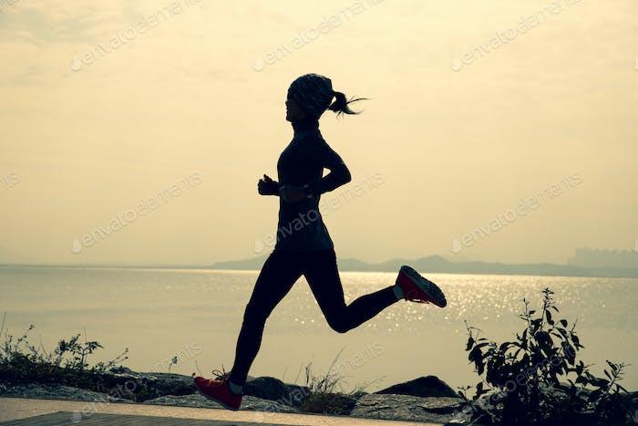Fitness mujer corriendo entrenamiento para maratón en el sendero de la costa soleada
