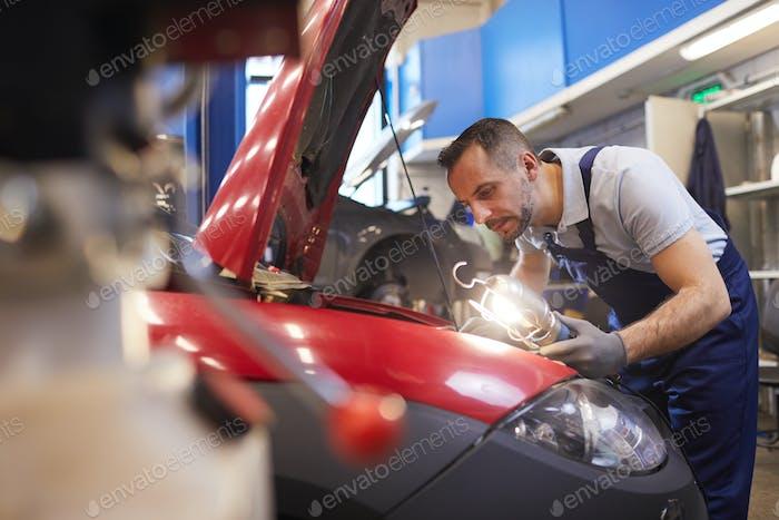 Mechanic Inspecting Car in Garage Workshop