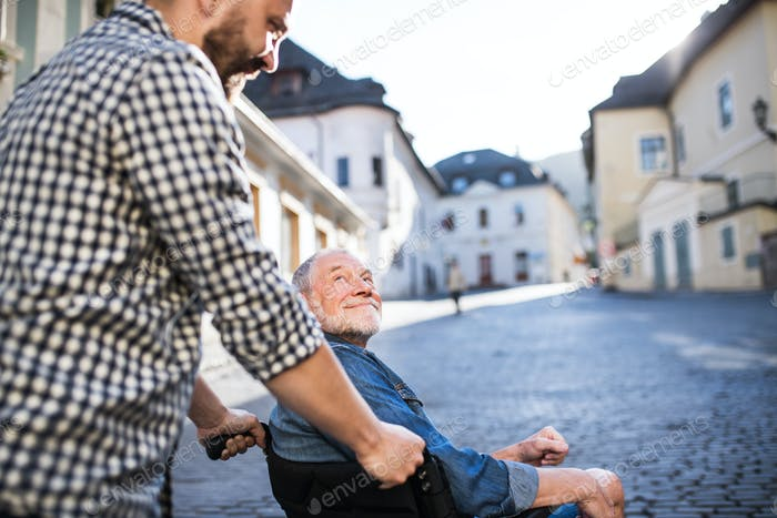 An adult son with senior father in wheelchair on a walk in town.