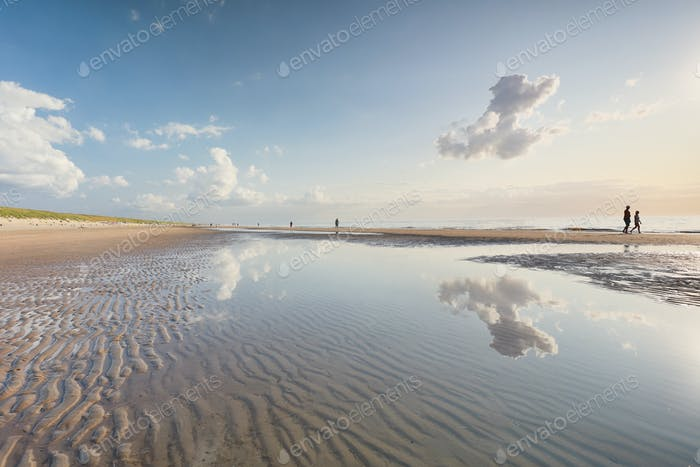 people silhouettes on North sea beach at low tide
