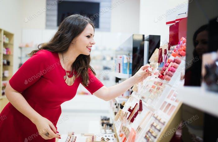 Beautiful woman testing lipsticks at cosmetics store