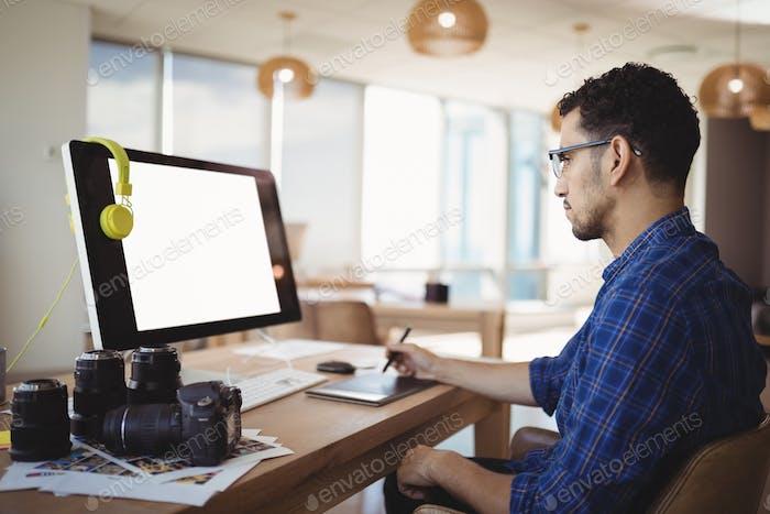 Diseñador gráfico atento Uso tableta gráfica en el escritorio