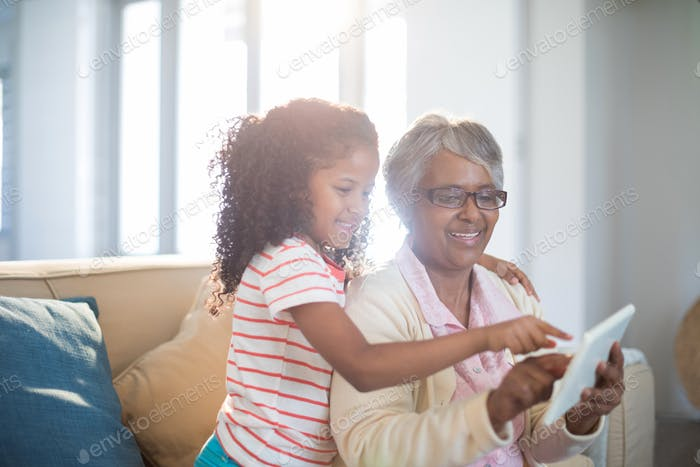 Smiling grandmother and granddaughter using digital tablet on sofa in living room