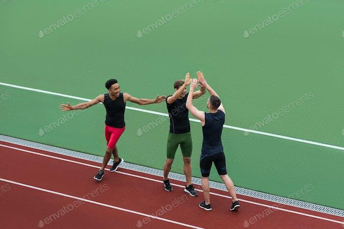 Multiethnic athlete team standing on running track