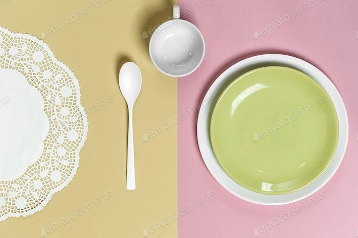 Servieren auf pastellrosa-grünem Hintergrund: hellgrüner Teller, Becher,