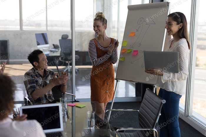 Female executives explaining business strategy with a flip chart board to their business colleagues
