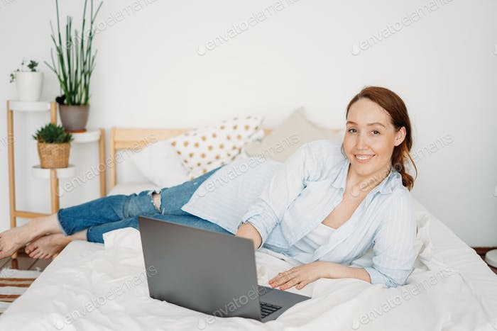 Working young adult brunette woman freelancer in casual clothes with laptop work at home