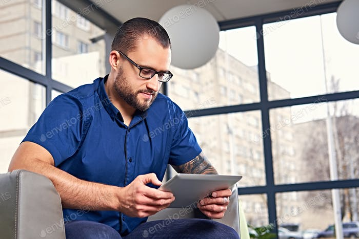 Bearded male in eyeglasses using a tablet PC.