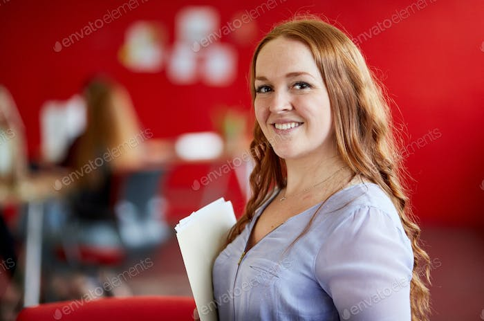 Confident female designer working and reviewing documents inside