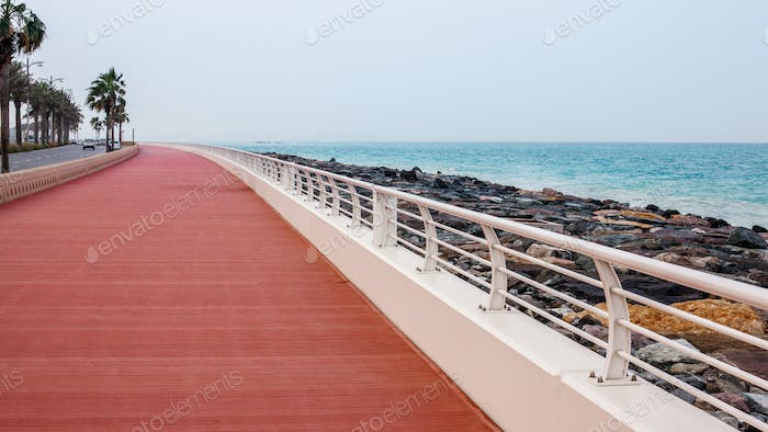 Promenade with walkway and white fence.