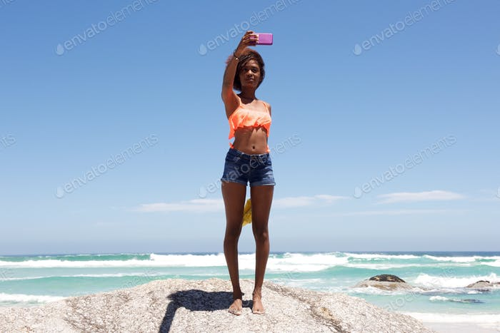 Young african woman taking selfie at the beach