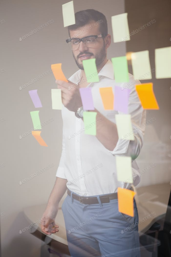 Casual businessman looking at sticky notes in the office