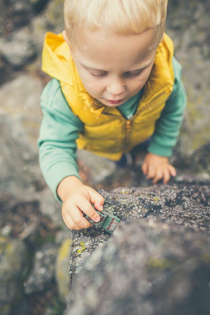 Enfant garçon jouant sur un rocher