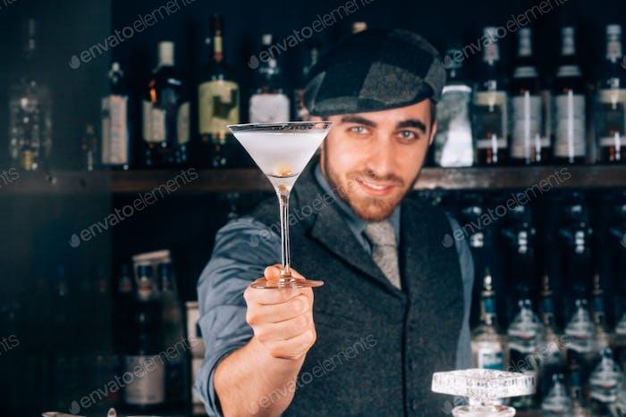 Barmann bereitet und serviert trockenen Martini-Cocktail in Martini-Glas.