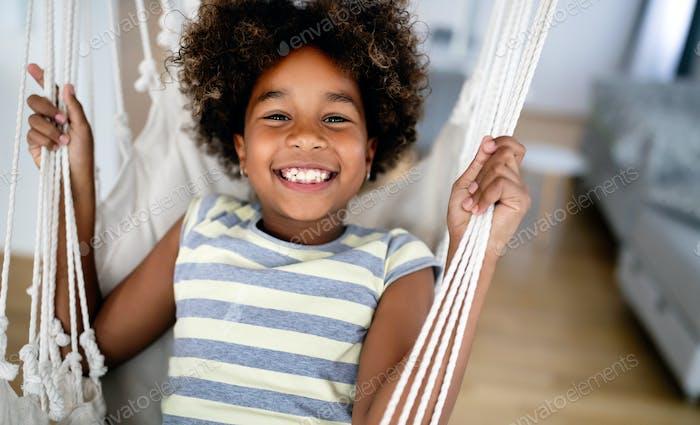 Adorable girl enjoying on indoor swing in living room