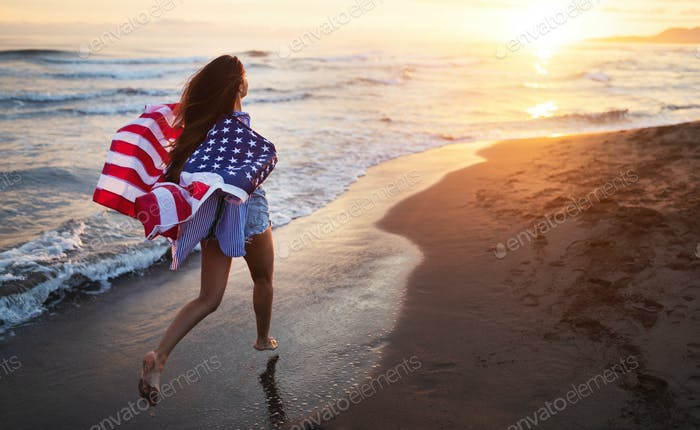 Cheerful happy woman outdoors on the beach holding USA flag having fun