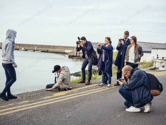 Friends photographing woman walking road by river against sky