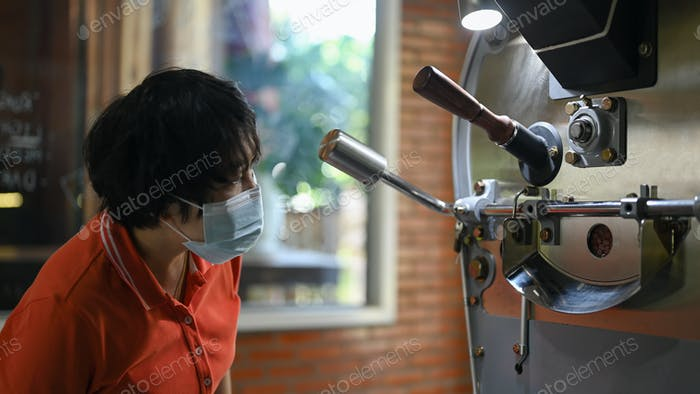 Coffee developers wearing mask are controlling the roasting process.